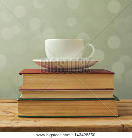 Coffee cup on old books over dreamy background