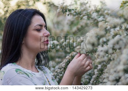 Beautiful woman in the flowered garden. People