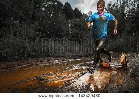 Trail running athlete crossing the dirty puddle in the rural road