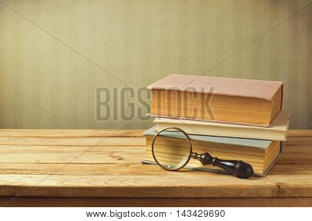 Old books with vintage magnifying glass on wooden table