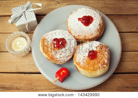Donuts with jam for Jewish Holiday Hanukkah over wooden background