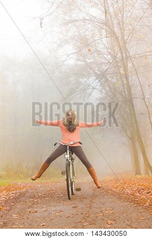 Happy carefree active woman having fun riding bike bicycle in fall autumn park. Crazy young girl in sweater relaxing. Healthy lifestyle and recreation leisure activity.
