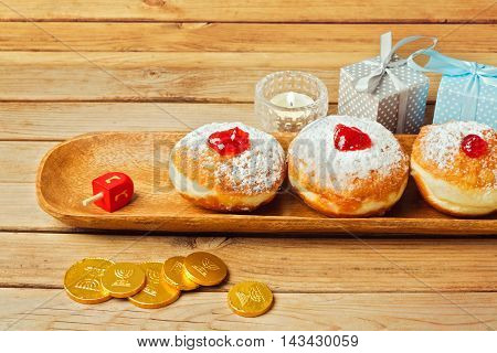 Donuts with jam on wooden plate for Jewish Holiday Hanukkah