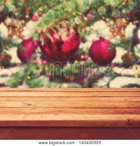 Christmas background with empty wooden deck table over Christmas tree decorations