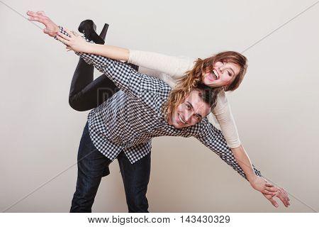 Woman Riding Piggyback On Man. Happy Couple.