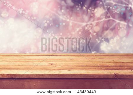 Beautiful winter bokeh background and wooden table. Ready for product montage