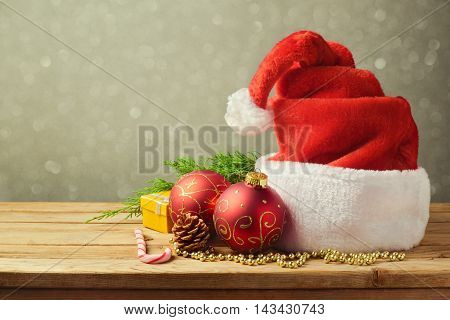 Santa Hat with Christmas decorations on wooden table
