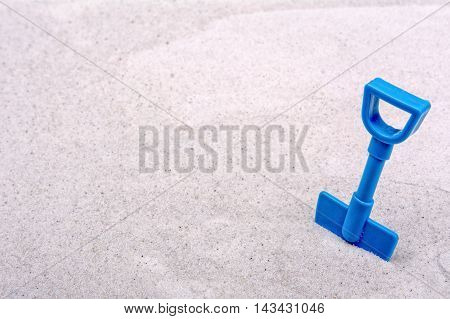 Blue scoop on a grey sand background