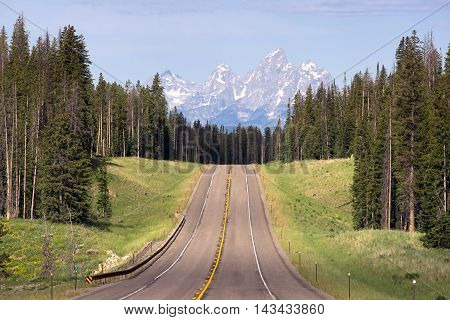 The Rocky Mountains rise up in the distance over the highway