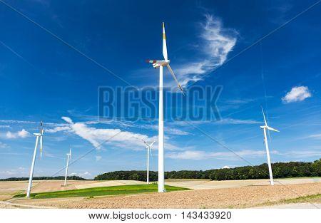 Wind turbine farm on a hillside in Germany. Sunny summer day.