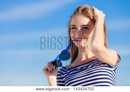 Summer relaxation concept.. Portrait girl with blue heart shaped sunglasses enjoying summer breeze outdoor on sky background
