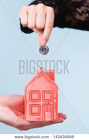 Savings for future plans. People hands with red little house piggy bank and silver coin. Money loin for family home better life.