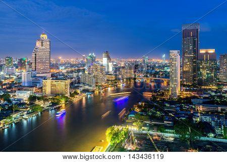Bangkok skyline along Chao Phraya river at night in Bangkok Thailand.