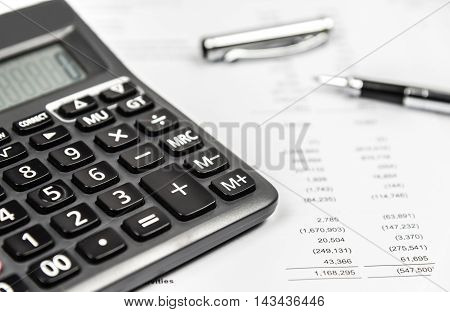 Calculator and pen on financial statement paper. Business accounting concept.