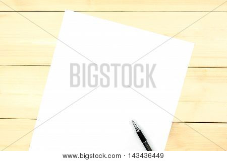Blank paper with copyspace on wooden background.