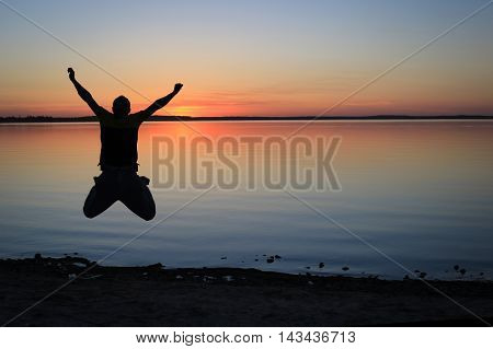 Silhouette of a Man Jumping on the Lakeshore at Sunset