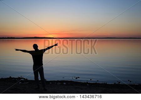 Silhouette of Man with Outstretched Arms in the Sunset