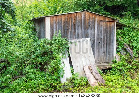Old wooden shed in the forest. Building materials in the foreground.