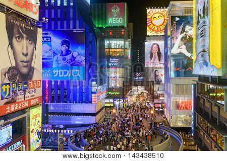OSAKA, JAPAN - AUGUST 16, 2015: Pedestrians walk below billboards in the Dotonbori district. The district is a popular tourist attraction.