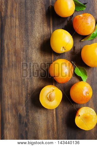 Yellow plums on wooden background with copy space. Stone fruits