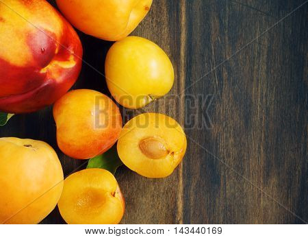 Stone fruits on wooden background. Yellow plums apricots and nectarines