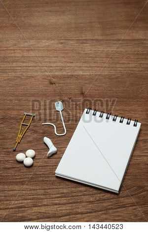 Miniature items of illness or injury beside memo pad. Injury, illness, medical, insurance concept.