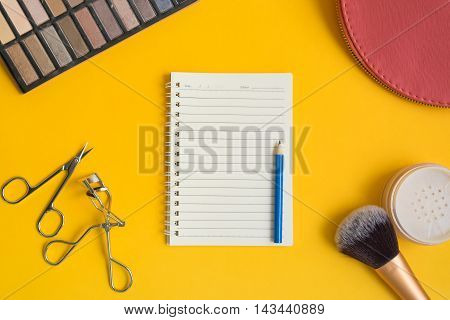 Top view of an open notepad and blue pencil surrounded by cosmetic items - eyeshadow brush powder scissors mascara eyelash curler and bag on yellow background