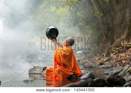 Novice sitting at the waterfall at rural area .