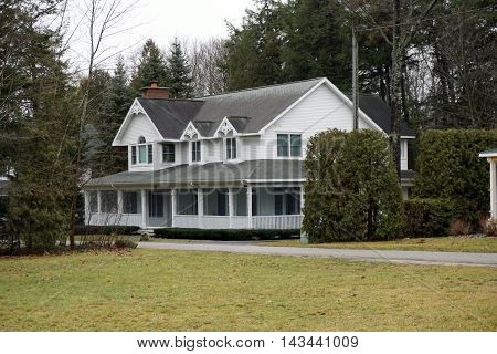 WEQUETONSING, MICHIGAN / UNITED STATES - DECEMBER 22, 2015: A large white home with a wraparound porch on Pennsylvania Avenue in Wequetonsing.