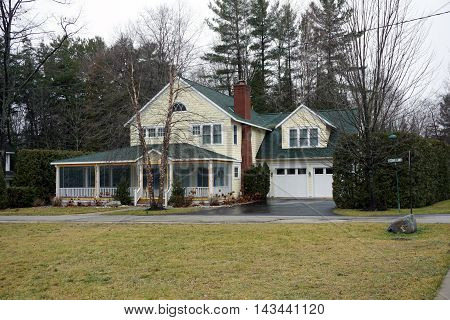 WEQUETONSING, MICHIGAN / UNITED STATES - DECEMBER 22, 2015: A large yellow home with an attached garage on Cedar Lane in Wequetonsing.