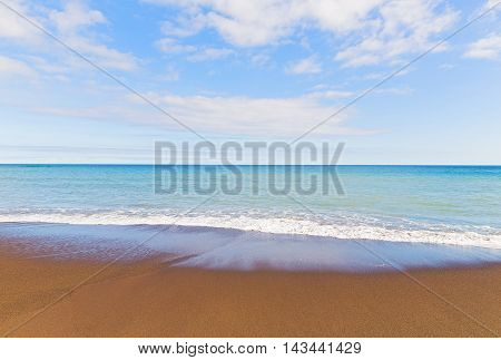 Ocean wave tracery on an empty sandy beach of Sao Miguel Island Portugal. Beach with volcanic sand in Azores Portugal.