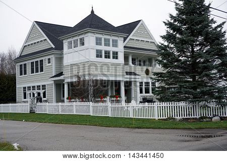 WEQUETONSING, MICHIGAN / UNITED STATES - DECEMBER 22, 2015: A large home with a white picket fence on Pennsylvania Avenue in Wequetonsing.