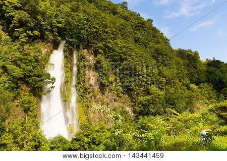 Scenic waterfall near Furnas in Azores Portugal. Rain forest on a hill and waterfall in sight on Sao Miguel Island.
