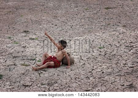 Children sits down and points up in the dried soil in arid season.