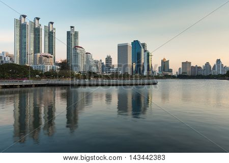 City building view in water pool of public park, Bangkok Thailand