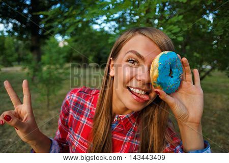 Funny girl holding a donut in hand closing one eye. Delicious.
