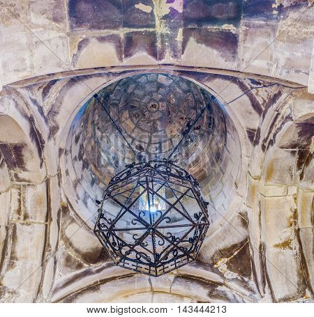 DILIJAN ARMENIA - MAY 31 2016: The stone dome and interesting forged chandelier in Astvatsatsin Church in Haghartsin Monastery on May 31 in Dilijan.