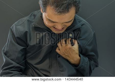Asia man pain from disease heart attack in black background