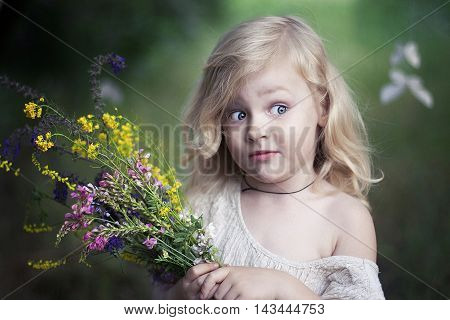 Little girl with a bouquet of wildflowers. Portrait of a funny girl with a bouquet of flowers. Surprised blonde girl with colorful bouquet.