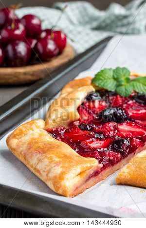 Cottage cheese dough galette with strawberry and cherry on baking tray vertical