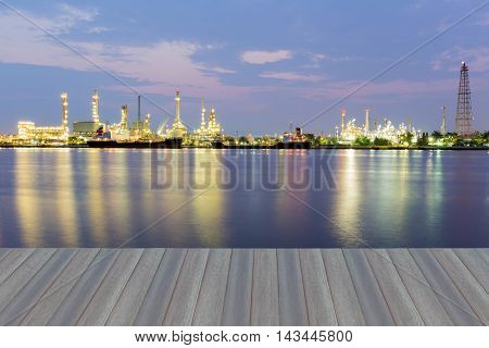 Opening wooden floor, Oil refinery industry plant during twilight morning along with water reflection