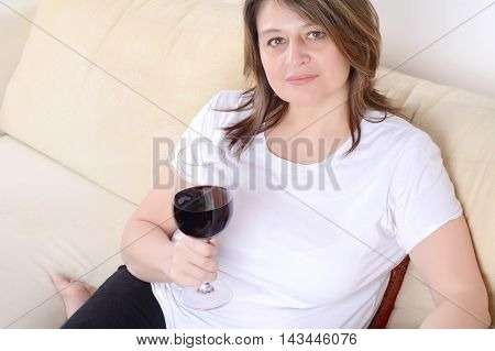 Portrait of a beautiful woman relaxed on sofa with a glass of wine. Indoors.