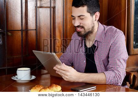 Portrait of young latin man using digital tablet with cup of coffee and smartphone at a cafe. Indoor.