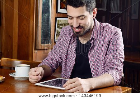 Portrait of young latin man using digital tablet with cup of coffee at a cafe. Indoor.
