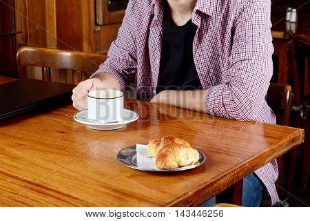 Portrait of young latin man with laptop and cup of coffee at a cafe. Indoors.