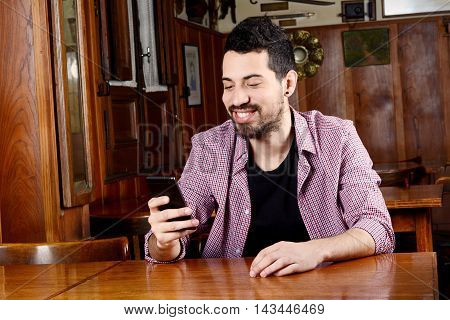 Portrait of young latin man using his smartphone at a cafe. Indoors.