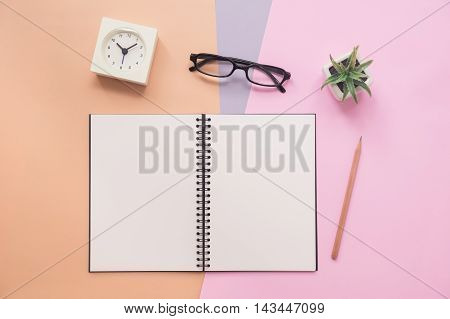 Top view of open empty spiral notebook with pen eyeglasses clock and plant on pastel colorful background