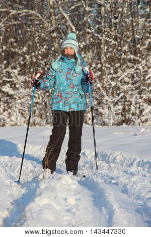 a girl in a blue jacket is skiing in the winter snowy forest