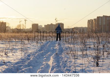 a girl in a blue jacket is skiing in the winter snowy meadow toward the city