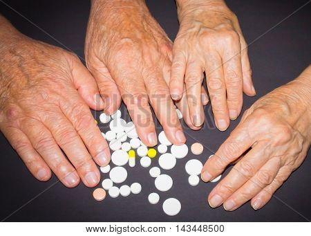 The old female and male hands with pills on black background
